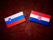Slovensk flagga med den kroatiska flaggan på en trädstubbe Royaltyfri Fotografi