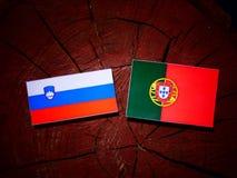 Slovensk flagga med den portugisiska flaggan på en isolerad trädstubbe Fotografering för Bildbyråer