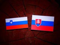 Slovensk flagga med den slovakiska flaggan på en isolerad trädstubbe Royaltyfri Fotografi