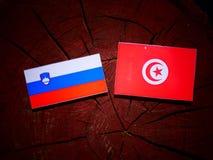 Slovensk flagga med den tunisiska flaggan på en isolerad trädstubbe Arkivbilder