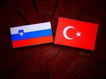 Slovensk flagga med den turkiska flaggan på en trädstubbe Fotografering för Bildbyråer