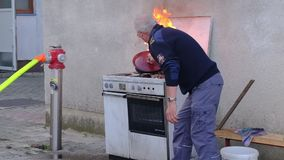 Blaze in the kitchen, hpt fat pan on fire, firefighter extinguishes fire with a lid. Slovenska Bistrica, Slovenia - Oct 4 2019: Firefighter demonstrates stock footage