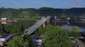 Slow aerial approach to Ambridge bridge. 10287 A slow, early morning aerial approach to the Ambridge Bridge spanning the Ohio River. Old factories and coal stock video