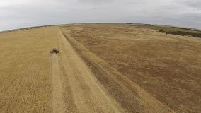 Slow Aerial shots of harvester at work on farm stock video footage