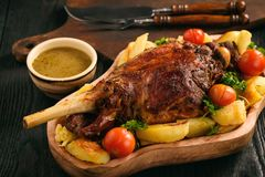Slow baked lamb leg with potatoes and sauce. Slow baked lamb leg with potatoes and sauce stock image