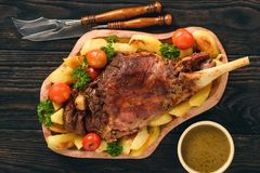 Slow baked lamb leg with potatoes and sauce. Royalty Free Stock Image