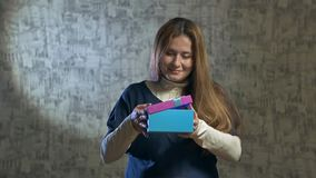 Beautiful girl opens a blue gift. Slow. beautiful girl opens a blue gift. Shakes the blue gift box and opens it stock video