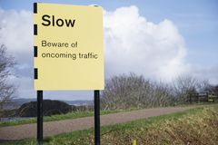 Slow beware of oncoming traffic sign road safety. Uk stock photo