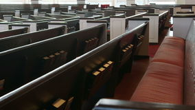 Slow camera move (dolly) shot along church pews. The camera slowly moves (dollies) past wooden pews in a Christian church stock video footage