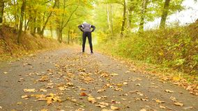 Slow camera movement. Sportsman in  black sortswear run on road. The man is slowly running on asphalt way covered by autumn leaves stock video