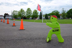 Slow! Children Crossing Sign. A sign for traffic to slow down is placed in parking area with children playing in field in the background stock photography
