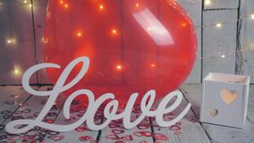 Slow close-up slide shot of Love sign with red hearts, lights and red baloon on background. Valentines day. Slow close-up slide shot of Love sign with red stock video footage