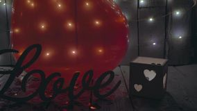 Slow close-up slide shot of Love sign with red hearts, lights and red baloon on background. Valentines day. stock footage