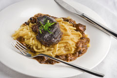 Slow cooked pork cheeks in gravy with spaetzle noodles Stock Image