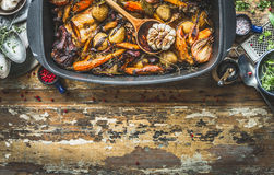 Slow cooked rabbit stew with  forest mushrooms and garden vegetables of season. Rabbit ragout on rustic kitchen table with cooking Royalty Free Stock Photography