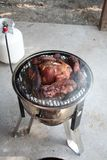Slow cooking country style ribs and chicken on a gas powered smoker on patio stock photography