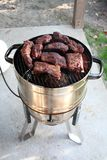 Slow cooking ribs on a gas powered smoker on patio. Slow cooking ribs on a gas powered smoker on patio Stock Image