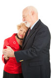 Slow Dancing. Senior couple doing a romantic slow dance. Isolated on white royalty free stock image