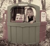 Slow day At The Kissing Booth. Little girl is having a slow day at the kissing booth Royalty Free Stock Photos