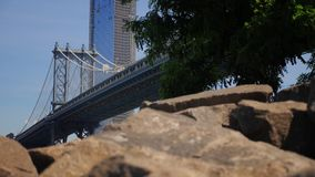 Slow Dolly Reveal of Manhattan Bridge in Summer. A slow dolly reveal establishing shot of the Manhattan Bridge as seen from Brooklyn shore. Shot at 60fps stock footage