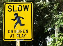 Slow down children at play sign. A yellow sign on the side of the road, slow down children at play royalty free stock photo