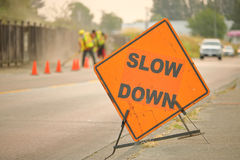 Slow Down Construction Sign. A large, English construction sign reminds motorists to slow down while road construction is underway royalty free stock photography