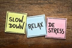 Slow down, relax, de-stress concept. Motivational lifestyle reminders on colorful sticky notes against rustic wood Stock Photos