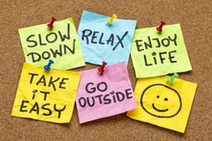 Slow down, relax, take it easy. Enjoy life -  motivational lifestyle reminders on colorful sticky notes Stock Images