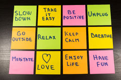 Slow down, relax, take it easy, keep calm, love, enjoy life, have fun and other motivational lifestyle reminders on colorful stick Royalty Free Stock Image