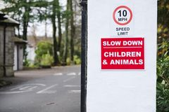 Slow down road safety caution children and animals at zoo entrance stock image