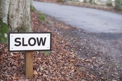 Slow down road safety sign on rural countryside highway uk. Scotland stock photography