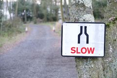 Slow down road safety sign on rural private countryside highway. Uk stock photos