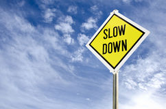 Slow Down road sign. Slow Down yellow road sign on blue sky with clouds background royalty free stock images