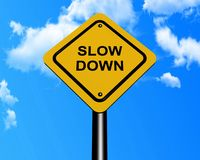 Slow down sign. Yellow diamond shaped slow down sign with blue sky and cloudscape background Stock Photos