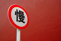 Slow down sign in Chinese. With red wall as background royalty free stock photo