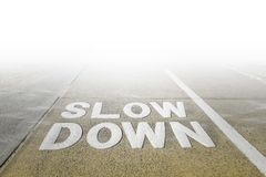 Slow Down sign on a footpath. Big Slow Down sign on a footpath disappearing in white fog stock photography