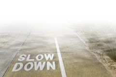 Slow Down sign written on shared footpath. Slow Down sign written on shared footpath for cyclists and pedestrians vanishing under low clouds and fog stock photos