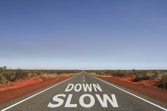 Slow down  written on the road. Slow down written on white on the road, safety message Royalty Free Stock Photography