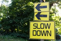 Slow Down yellow road sign green bush at background royalty free stock photos