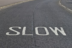 Slow down your speed. White text on Road for reducing speed Royalty Free Stock Image