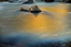 River Glass. Slow exposure of a river with the orange glow from the sun setting sky Stock Images