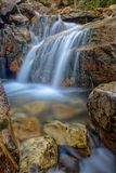 Back and Forth Over Rock. Slow exposure waterfall flowing over rocks and moss Stock Photos