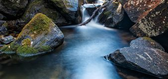 Summer Ice. Slow exposure of a waterfall going through rocks and moss Royalty Free Stock Photo
