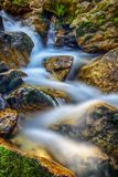 Blue to White Falls. Slow exposure of a waterfall going through rocks and moss Royalty Free Stock Images