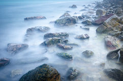Slow exposure waves and rocks on the beach Royalty Free Stock Photos