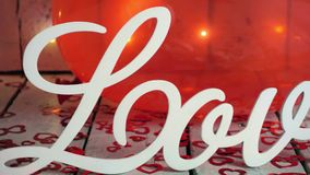 Slow extreme close-up slide shot of Love sign with red hearts, lights and red baloon on background. Valentines day. Slow extreme close-up slide shot of Love stock footage