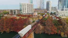 Slow forward aerial view of cargo train and Austin City Skyline. A slow forward aerial establishing shot of a cargo train traveling over a railroad bridge over stock video footage