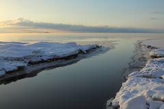 Slow freezing river flowing into the sea. River's mouth, winter beginning, freezing water, evening-glow Stock Images