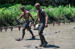 Slow going mud. Two teens walk carefully through slick mud on their way to the next obstacle at the 2012 mudathlon Stock Images
