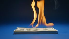 Slow motion: heap of paper money us dollar flaming on a table stock video